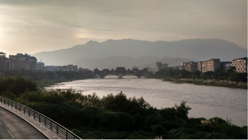 The city of Ya'an showcasing its many mountains, historical architecture on its mall bridge, and the Qingyi River.